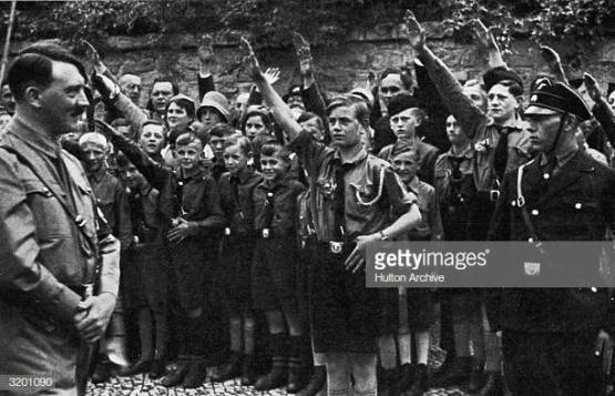 1933: Nazi leader Adolf Hitler smiles while uniformed Saxon youths salute him outdoors in Erfurt, Germany. (Photo by Hulton Archive/Getty Images)