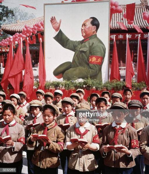 circa 1968: A group of Chinese children in uniform in front of a picture of Chairman Mao Zedong (1893 - 1976) holding Mao's 'Little Red Book' during China's Cultural Revolution. (Photo by Hulton Archive/Getty Images)