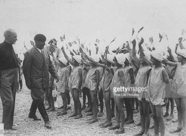 Italian fascist dictator Benito Mussolini (2L) walking past group of little girls waving flags towards him in admiration, on recently reclaimed Pontine Marshes. (Photo by Time Life Pictures/Pix Inc./The LIFE Picture Collection via Getty Images)